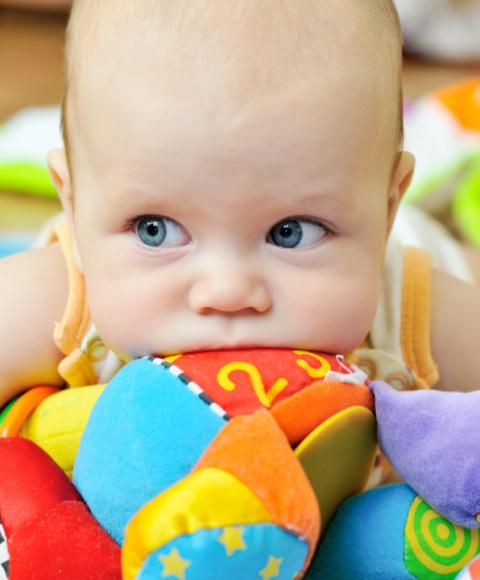 Beba s igračkom u ustima